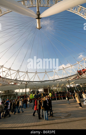 Tourists queueing up to have a ride on the London Eye - Stock Photo