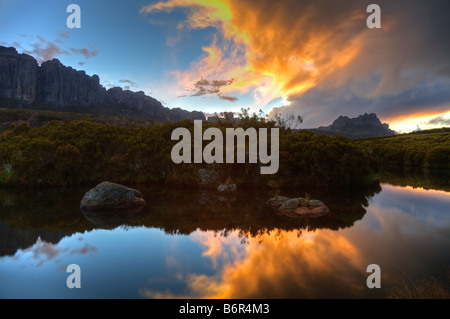 clouds reflected in still lake waters at dusk at Parc National Andringitra Fianarantsoa Madagascar - Stock Photo