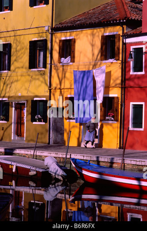 Local woman walks along canal on Burano, an island in the Venetian lagoon. Picturesque fishermen's houses line the - Stock Photo