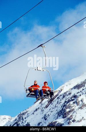 Couple of skiers on chair lift. Candanchu Ski Resort. Huesca province. Aragon. Spain. - Stock Photo