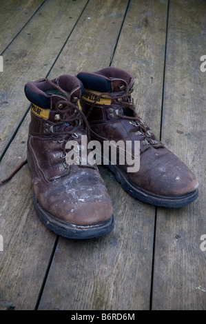 A pair of old brown leather Caterpillar walking boots on a wooden floor tough as old boots - Stock Photo