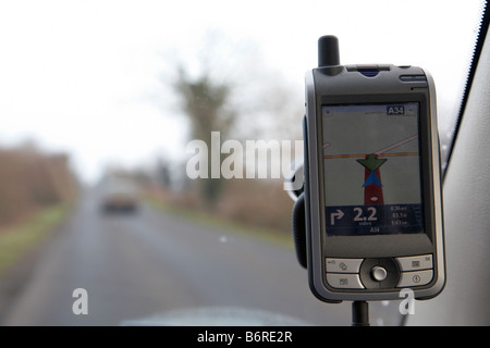 sat nav showing u turn on a pocket pc attached to a car windscreen on a country road - Stock Photo