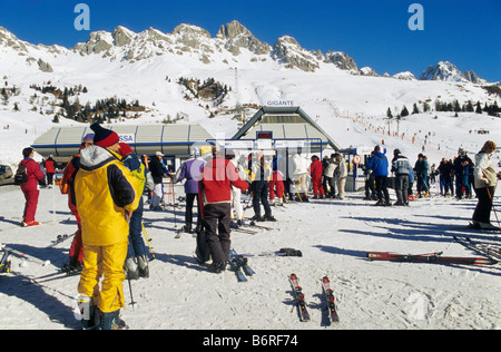 Skiers in line to chairlift at skiing area at Passo di San Pelegrino in Marmolada mountain group in winter Dolomites - Stock Photo
