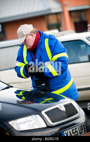 A private car park attendant wearing blue jacket taking the details of  cars parked in his electronic notebook, - Stock Photo