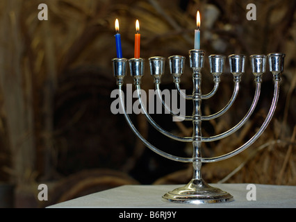 A Chanukia the main symbol of Chanukah The Jewish festival of light with 3 lit candles for the second day - Stock Photo
