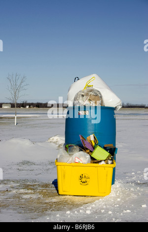 A blue trash can and a yellow recycle bin are full sitting in the snow. - Stock Photo