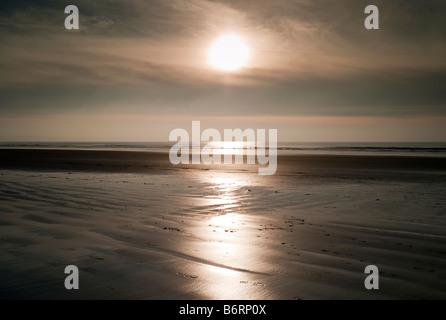 Lone jogger on Newgale Beach, Pembrokeshire, Wales - Stock Photo