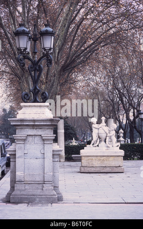 Statue and street lamp on Paseo del Prado near Plaza de la Cibeles, Madrid, Spain - Stock Photo