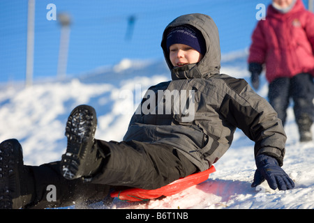 Brave little boy slides on plastic bob from hillside with high speed - Stock Photo