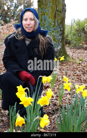 A winters day as Megan crouches behind some Daffadils at Orange Botanic Gardens, NSW Australia - Stock Photo