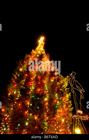 christmas tree lights at night figure in old fashioned clothes and top hat at night dark - Old Fashioned Christmas Tree Lights