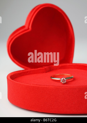 heart-shaped valentines day box with lid off and diamond ring inside on white background - Stock Photo