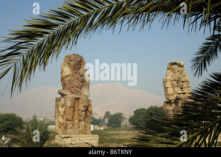 The Colossi of Memnon are two massive stone statues of Pharaoh Amenhotep III on the West Bank of the River Nile. - Stock Photo