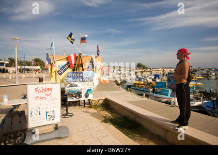 Man reading advertisements for water activities at seaside, Cyprus - Stock Photo