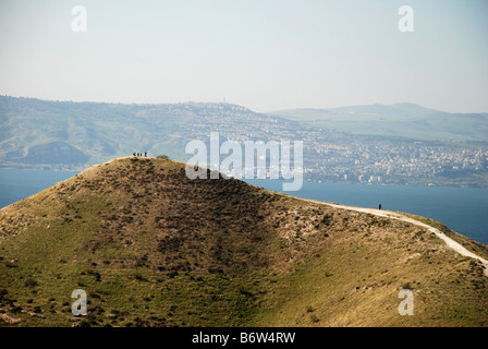 Inspirational view of hikers above the Golan mountain plateau over looking the Sea of Galilee. - Stock Photo