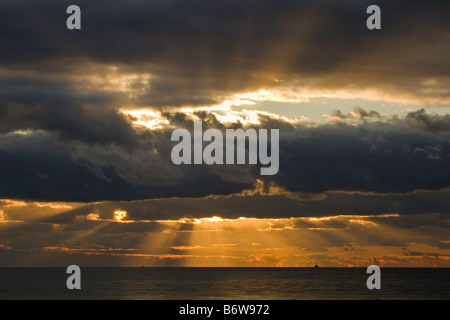 The sun rays of a sunset shine out from behind the cloud as seen from the cliffs at Birling Gap beach near Eastbourne - Stock Photo
