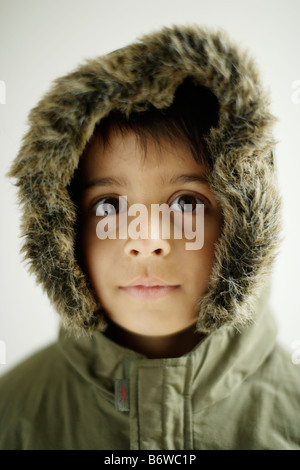 Child wears Parka coat with hood zipped up Boy aged six years - Stock Photo