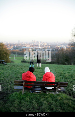 Two people sitting on a bench at the top of Parliament Hill, Hampstead Heath, London. - Stock Photo