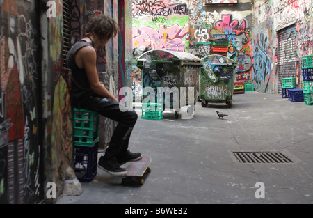 Young skateboarder hanging out in a graffiti alley in Melbourne,Australia. - Stock Photo