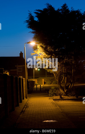 deserted empty footpath in a town at night illuminated by lights from lamppost UK - nobody no people - Stock Photo
