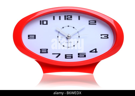 Red retro oval shaped clock cut out isolated on white background - Stock Photo