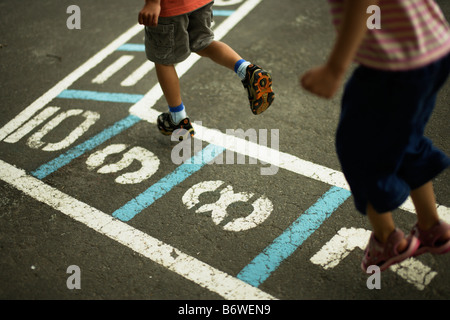 Children play hopscotch in a school playground - Stock Photo