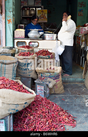 INDIA JAIPUR RAJASTHAN Tiny shop in the market area of old Jaipur selling bright colored dried red chili peppers - Stock Photo