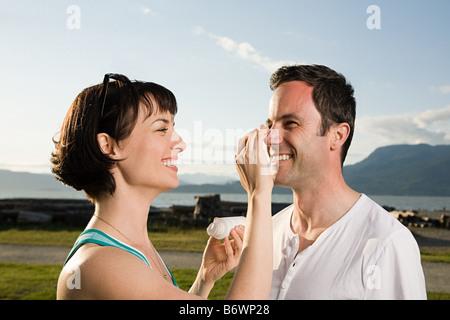 Couple applying suntan lotion - Stock Photo