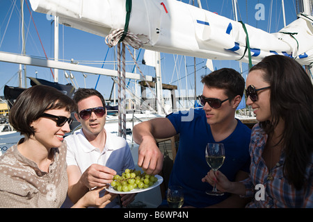 Friends eating grapes on a boat - Stock Photo