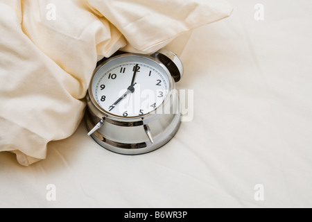 Alarm clock on bed - Stock Photo