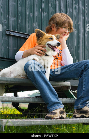 Boy sitting on a step with his dog - Stock Photo