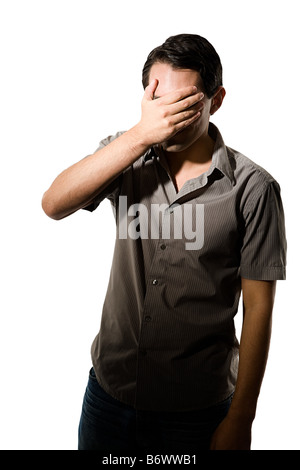 Young man covering his eyes - Stock Photo
