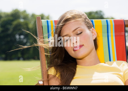 Young woman in deckchair - Stock Photo