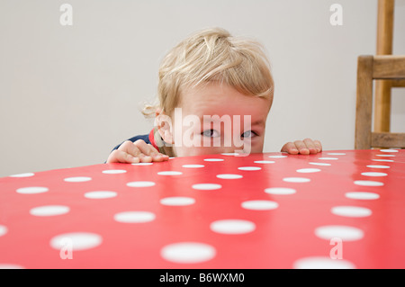 Boy looking over table - Stock Photo
