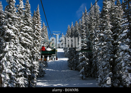 USA, Colorado, Vail Ski Resort. Skiers being carried on a chair lift in Vail back bowls - Stock Photo