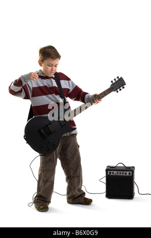 A boy about to hit a chord on a matt black electric guitar with amplifier isolated on a white background - Stock Photo