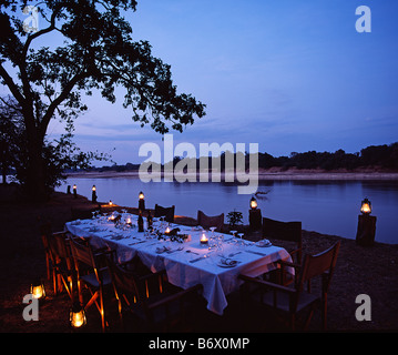 Zambia, South Luangwa national park. Candlelit dinner table on the bank of the Luangwa River, Mchenja bushcamp. - Stock Photo