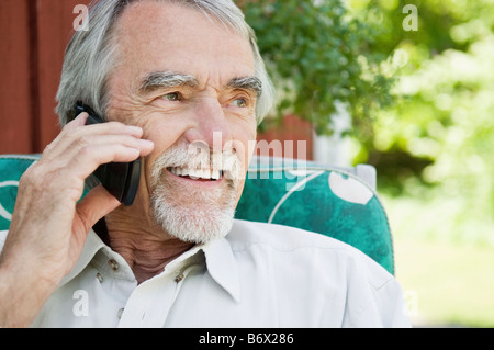 Man with beard speaking on the cell phone - Stock Photo