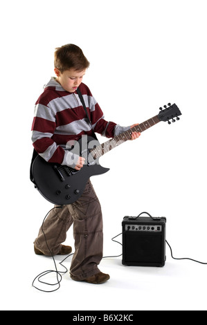 A boy playing a matt black electric guitar with amplifier isolated on a white background - Stock Photo