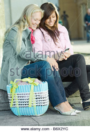 Two friends sitting with mobile phone - Stock Photo