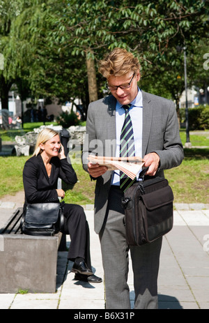 Businessman and businesswoman in park - Stock Photo