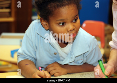 Young African American girl coloring pictures with crayons on a desk - Stock Photo