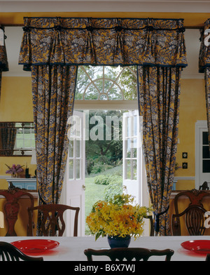 Patterned Curtains With Matching Pelmet At Open French Doors In Yellow Country Dining Room