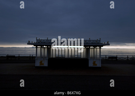 A promenade shelter against a darkening sky on the prom on Brighton and Hove seafront - Stock Photo