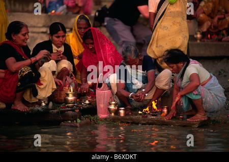 india, varanasi, ganges river, women giving offerings at dawn