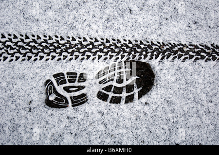 tyre and trainer tracks left in the snow by runners and cyclists defying the weather. - Stock Photo