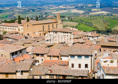 Aerial view of the village of San Gimignano with orange tiled rooftops of the houses and church of St Augustine - Stock Photo