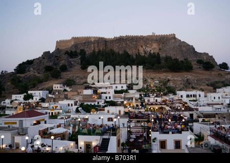 View over illuminated town in the evening to Acropolis, people sitting on terraces of restaurants, Lindos, Rhodes, - Stock Photo