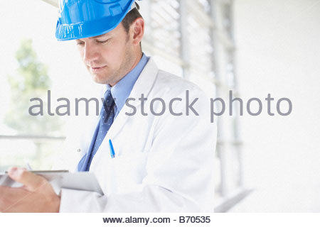 Businessman in hard-hat writing on clipboard - Stock Photo