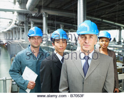 Businesspeople wearing hard-hats in warehouse - Stock Photo